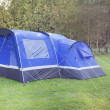 Blue tent in shaded area near woods - Stock Photo