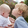 Little boy kisses his baby sister — Stock Photo