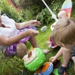Foto Stock: Gran and gran children playing outside in the garden