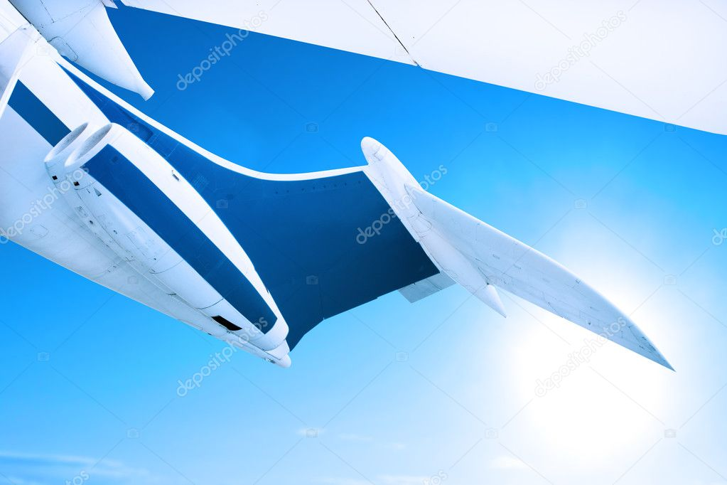 Airplane flying against a blue sky, close up of tail fin and engines — Zdjęcie stockowe #8752785