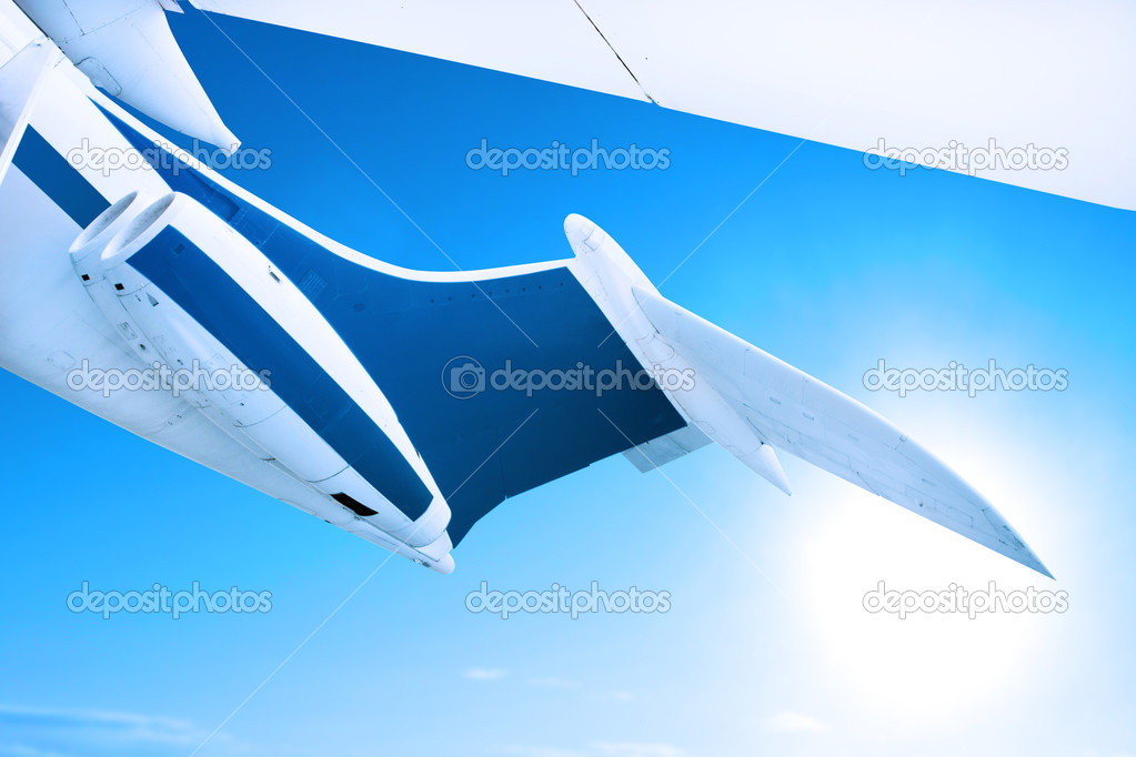 Airplane flying against a blue sky, close up of tail fin and engines  Photo #8752785