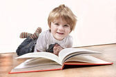 Young 4 year old boy reading a book — Stock Photo