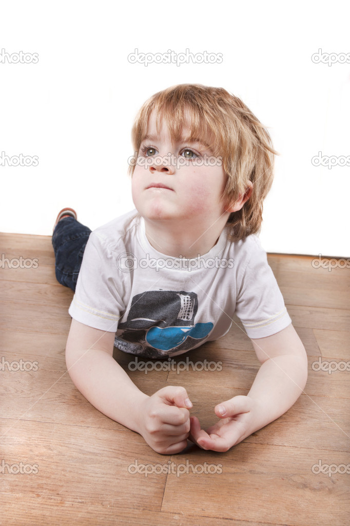 Isolated white wall background of young child latying on the floor thinking looking up — Stock Photo #8956964