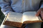 Man reading old German Bible in sunlight — Stock Photo