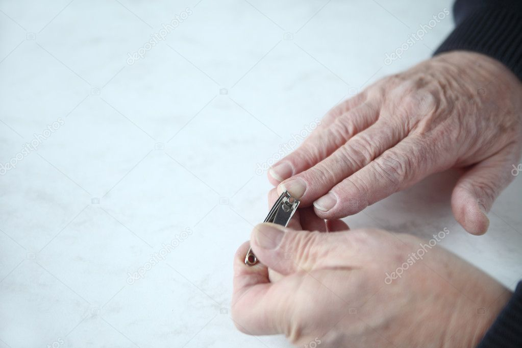 Senior man clips his fingernails with space for text — Stock Photo #8941263