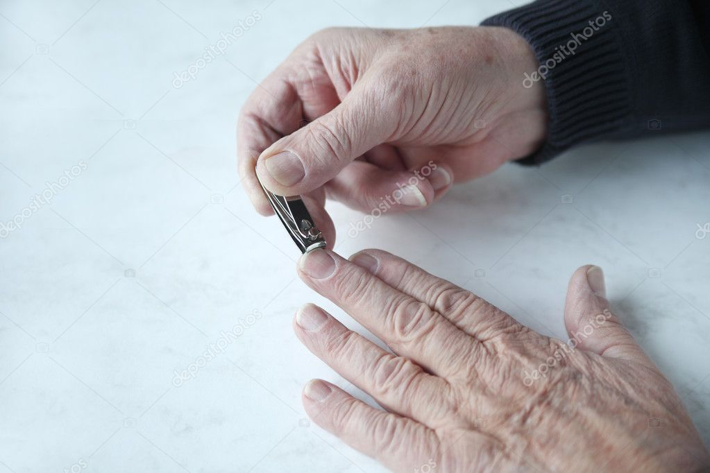 Senior man clips his fingernails with space for text  Stock Photo #8941271