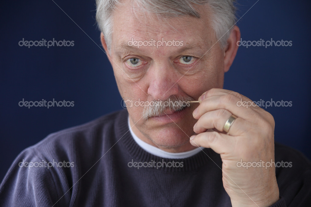 Older man cleans his teeth with a toothpick  Stock Photo #8941576