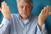 Older man with his hands up — Stock Photo