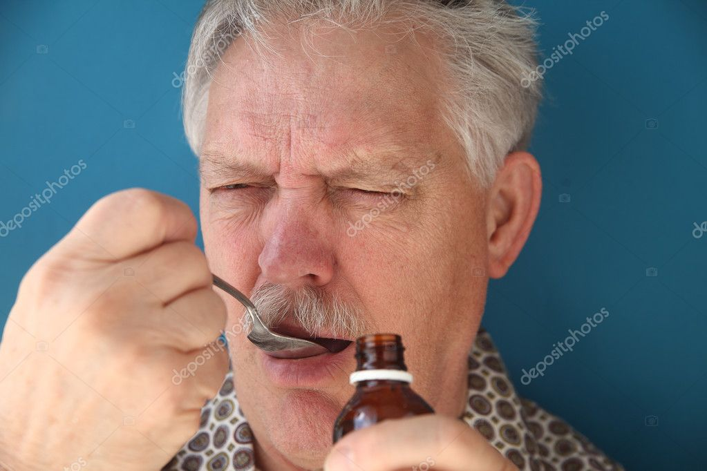 Sick man takes a spoonful of cough syrup — Stock Photo #9326670