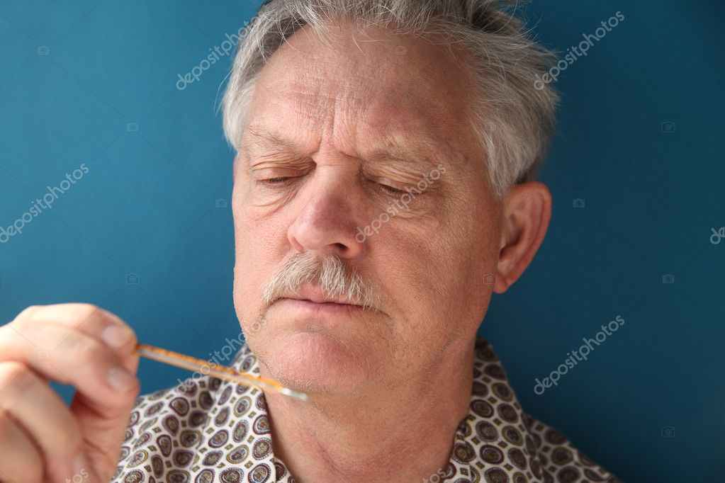 Older man frowns as he looks at his temperature — Stock Photo #9326746