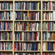 Bookshelf in library with many books — Stock Photo #10525852