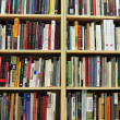Bookshelf in library with many books — Stock Photo #10525858