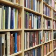 Bookshelf in library with many books - Stockfoto
