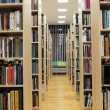 Bookshelf in library with many books — Stock Photo #10525871