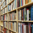 Bookshelf in library with many books — Stock Photo #10525885