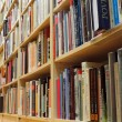 Bookshelf in library with many books — Stock Photo #10525894
