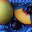 Grapes, peaches and apples in a blue bowl — Stock Photo