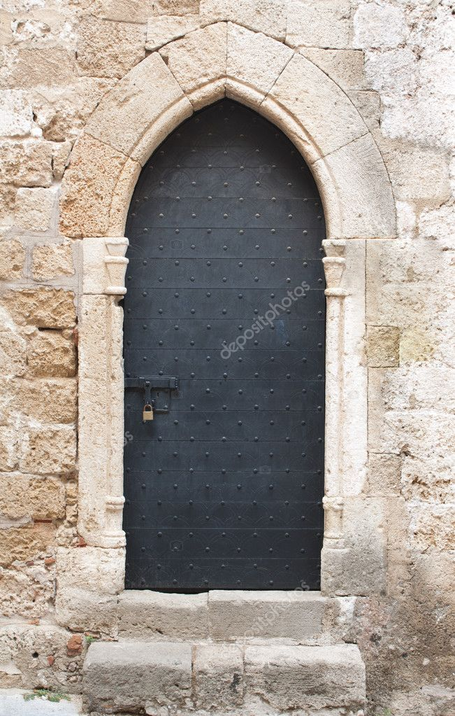Old black wooden medieval door on limestone wall with antique sliding door bolt and padlock. — Stock Photo #8823727
