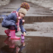 Girl playing in puddles — Stock Photo