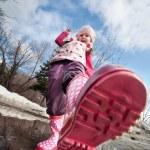 een beetje meisjes roze laarzen spetteren in een modderig Plas — Stockfoto