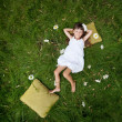 Stock Photo: Little girl resting on soft pillow in fresh spring grass