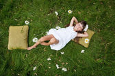 Little girl resting on soft pillow in fresh spring grass — Stock Photo