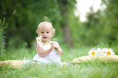 Baby sitting on green grass — Stock Photo