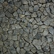 Stock Photo: Grungy weathered stone rubble mosaic wall surface.