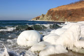 Ice covered stones on seashore — Stock Photo