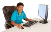 African American Nurse Smiling at Camera While Sitting at Desk — Stock Photo