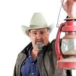Adult male cowboy holding lantern — Stock Photo #9980516