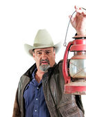 Adult male cowboy holding lantern — Stock Photo