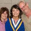 Stock Photo: Young Womin Graduation Gown with Family