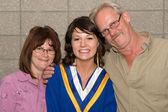 Young Woman in Graduation Gown with Family — Stock Photo
