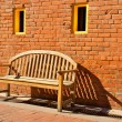Wooden Bench Sitting by Orange Brick Wall with Yellow Windows — Stock Photo
