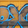 Yellow Boxcar With Blue Spraypaint - Stock Photo