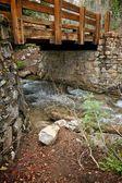 Wooden Bridge Between Stone Walls and Stream — Stock Photo