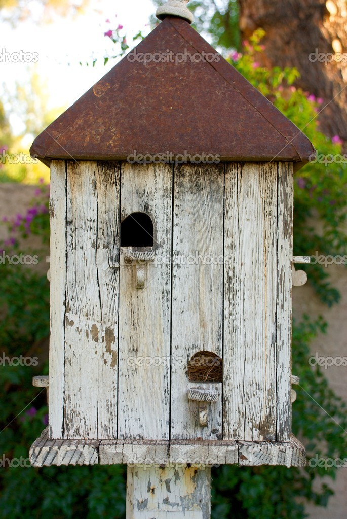 Vertical shot of an old birdhouse with a rusted metal roof  Stock Photo #10492665