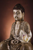 Buddha statue with orchid flower — Stock Photo