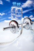 Fitness, dumbell and blue sky — Stock Photo