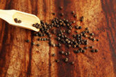 Pepper grains and wooden spoon — Stock Photo
