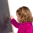 Royalty-Free Stock Photo: Little girl writing on a blackboard