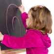 Little girl writing on a blackboard — Stock Photo