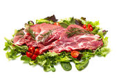 Sliced raw meat with salad — Stock Photo