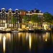 Colorful houses in Amsterdam at night - Stock Photo
