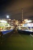 Amsterdam v noci - výletní loď nábřeží nedaleko damrac ulice — Stock fotografie