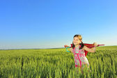 The little girl on a field with an umbrella — Stock Photo