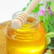 Stock Photo: Glass jar full of honey and stick with acacia pink and white fl