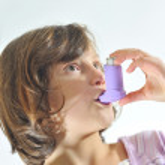 Girl using an inhaler for asthma — Stock Photo