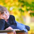 Little girl sitting on the bench in park — Stock Photo #9832041